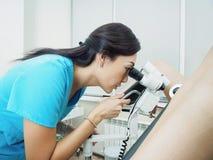 Undersökande patient för asiatisk gynekolog i sjukhus genom att använda en colposcope arkivbilder
