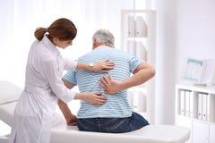 Undersökande patient för kiropraktor med baksida att smärta royaltyfri bild