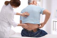Undersökande patient för kiropraktor med baksida att smärta royaltyfria foton