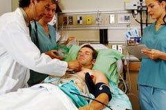 Undersökande patient för personal i nöd- avdelning Royaltyfri Fotografi