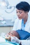 Undersökande pojketänder för kvinnlig tandläkare Royaltyfri Fotografi
