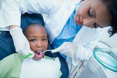 Undersökande pojketänder för kvinnlig tandläkare Royaltyfria Bilder