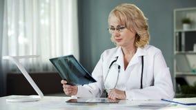 Undersökande röntgenstråle bild för blond kvinnlig doktor, medicinskt yrke, diagnos arkivbild