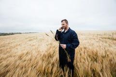 Undersökande skördar för bonde, medan tala på mobiltelefonen i fältet Royaltyfria Bilder
