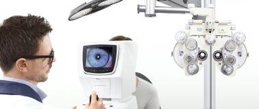 Undersökande synförmågapatient för optometriker i optikerkontor arkivfoto