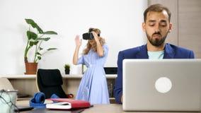 Undersökande virtuell verklighet för härlig kvinna, medan hennes pojkvän arbetar på datoren arkivfilmer