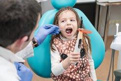 Undersökning av tänder för ett barn arkivbild