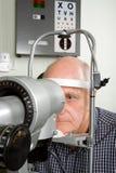 undersökningsöga som har den äldre mannen Arkivfoton