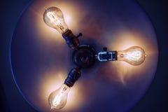 Undersida av en lampa med tre lightbulbs Arkivfoton