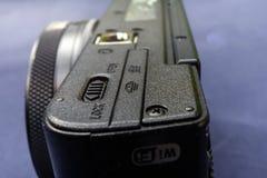 Undersida av en liten svart kompakt kamera, diagonal sikt till baksidan, lågt djup av fältet arkivbilder