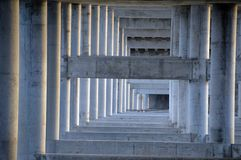 Underside bridge construction. A bridge under structure of concrete pilars and beams Stock Image