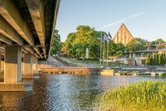 The underneath of a bridge. a river with a pyramid. The underside of a bridge. the view across a river. three flags on flagpoles. boats moored on a riverbank. a stock photos