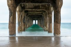 Underside of Manhattan Beach Pier. Blurry, soft water effect from long exposure under the sharp pillars of the pier Royalty Free Stock Images