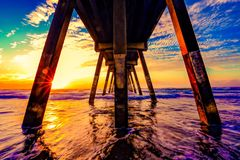 Underside of ocean jetty at sunset Stock Images