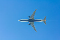 Underside of a passenger jet aircraft flying overhead Royalty Free Stock Images