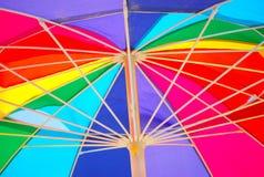 Underside of a rainbow colored beach umbrella Stock Photos