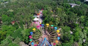 Underside or side view from ground of a ferris wheel over blue sky. Bright and colorful fragment of moving round ferris stock footage