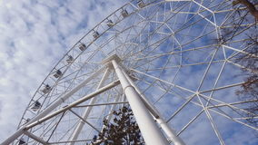 Underside view of a ferris wheel against blue sky with clouds. stock video footage