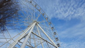 Underside view of a ferris wheel against blue sky with clouds. stock video