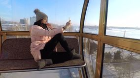 Underside view of a ferris wheel over blue sky. Girl doing selfie sitting in the cockpit of a ferris wheel on the phone smiling. Selfi girl in winter in a warm stock video footage