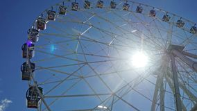 Underside view of a ferris wheel over blue sky and the sun in slow motion. 1920x1080. Hd stock video footage