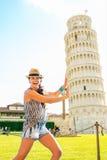 Understödjande lutande torn för rolig kvinna av pisa Arkivfoto