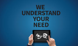 WE UNDERSTAND YOUR NEEDS. On the tablet pc screen held by businessman hands - online, top view stock photography