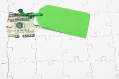 Understanding finances. Puzzle with money under it and green sale tag. understanding finances Royalty Free Stock Images