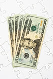Understanding finances. Puzzle with twenty dollar bills sitting on it. understanding finances Stock Photos