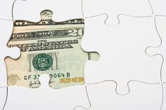 Understanding finances. Puzzle with money under it. understanding finances Royalty Free Stock Photography