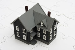 Understanding Mortgages. House sitting on a puzzle, the mysteries of the housing market Stock Image