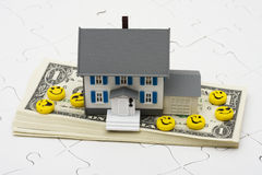 Understanding Mortgages. House sitting on stack of money with puzzle and happy faces. Understanding mortgages Stock Photography