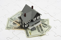 Understanding Mortgages. House sitting on money with puzzle. understanding mortgages Royalty Free Stock Photography