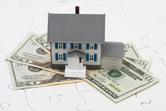 Understanding Mortgages. House sitting on money with puzzle. Understanding mortgages Stock Photos