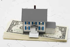 Understanding Mortgages. House sitting on stack of money with puzzle , understanding mortgages Royalty Free Stock Photos