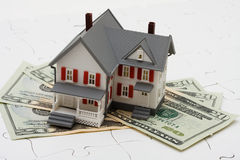 Understanding Mortgages. House sitting on money with puzzle. Understanding mortgages Stock Photo