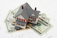 Understanding Mortgages. House sitting on money with puzzle. Understanding mortgages Stock Photography