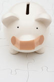 Understanding Personal Finances. Piggy bank sitting on white puzzle, understanding personal finances Stock Image