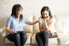 Understanding psychologist supporting and comforting patient. Understanding psychotherapist supporting and comforting pensive female patient sitting on couch Royalty Free Stock Image