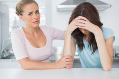 Understanding woman comforting her upset friend. Understanding women comforting her upset friend laid on the bar Royalty Free Stock Photography