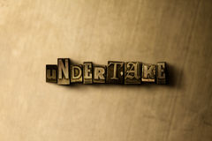 UNDERTAKE - close-up of grungy vintage typeset word on metal backdrop Royalty Free Stock Photography