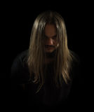 The undertaker in a black background. Frowning man looking like a rock star with a black t-shirt with long, beautiful, luscious hair looking forward Royalty Free Stock Images