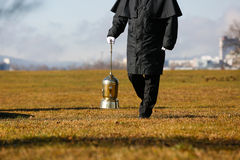 Undertaker carrying an urn with ashes of cremated human. Funeral director, undertaker, carrying an extravagant urn with ashes of a cremated human during a formal Royalty Free Stock Photography