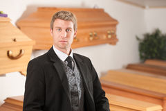 Undertaker in his store. With a display of coffins Royalty Free Stock Image