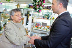 Undertaker shaking hand elderly lady Stock Images