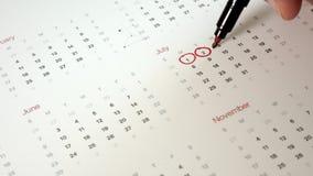 Underteckna dagen i kalendern med en penna, dra en fästing stock video