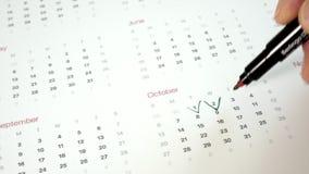 Underteckna dagen i kalendern med en penna, dra en fästing arkivfilmer