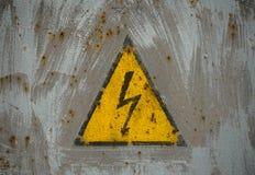 Underteckna den elektriska faran som förläggas på rostig metallpanel Royaltyfria Foton