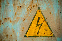 Underteckna den elektriska faran som förläggas på rostig metallpanel Fotografering för Bildbyråer