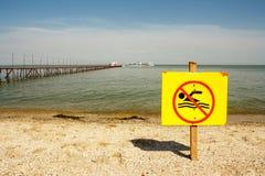 Underteckna ingen simning på bakgrunden av havet och pir Arkivbild